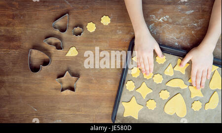 top view of child with raw shaped cookies on baking tray and cookie cutters on wooden table - Stock Photo