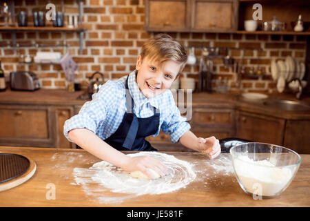 little boy making pizza dough on wooden tabletop in kitchen - Stock Photo