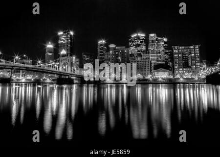 Black and white photo of the Pittsburgh, Pennsylvania skyline at night overlooking the Allegheny River with the - Stock Photo