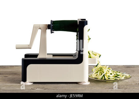 Lateral view of vegetable spiralizer making raw zucchini noodles (zoodles) . - Stock Photo