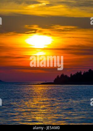 Sunset behind island - Stock Photo