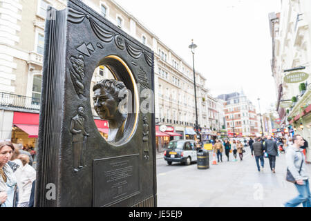 LONDON, UK - OCTOBER 26: Agatha Christie book shaped memorial with busy street in the background. The bronze memorial - Stock Photo