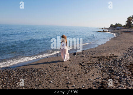 a young woman with brown hair walks on the beach, photographed from behind, no face - Stock Photo