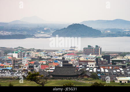 The view on a grey day from Seongsan Ilchulbong looking back onto the main Jeju island. - Stock Photo
