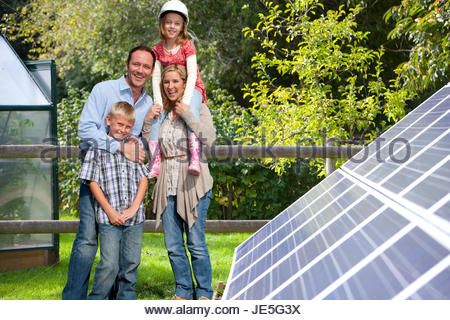 Happy family standing near large solar panels - Stock Photo