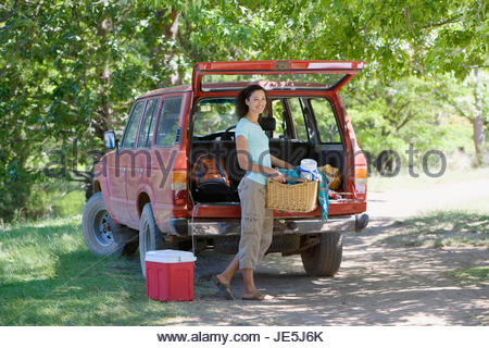 Woman unloading parked SUV on family camping trip, carrying picnic hamper, smiling, portrait - Stock Photo