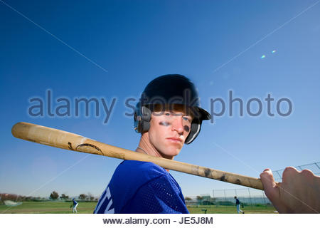 Baseball player, in blue uniform, helmet and face paint, standing on pitch with bat resting on shoulder, side view, - Stock Photo