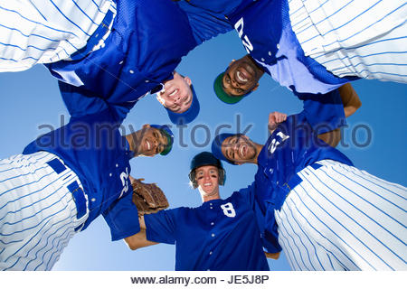 Baseball team, in blue uniform, standing in huddle, smiling, portrait, upward view - Stock Photo