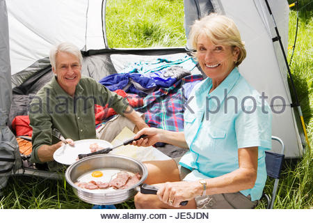 Senior woman serving husband fried breakfast on camping trip, man sitting inside tent, smiling, portrait - Stock Photo