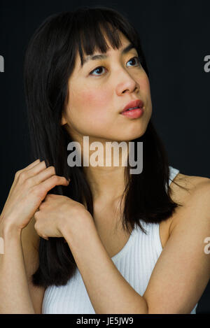 Young woman running hands through hair, looking away in thought - Stock Photo