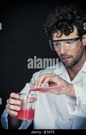 Chemist pouring liquid from test tube into beaker - Stock Photo