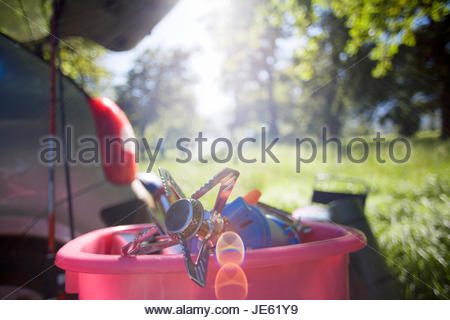 Parked car in woodland clearing, focus on camping stove in pink container (backlit) - Stock Photo