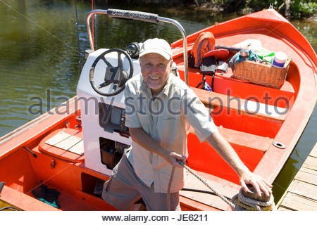 Senior man standing in motorboat beside lake jetty, tying rope to mooring post, smiling, portrait - Stock Photo
