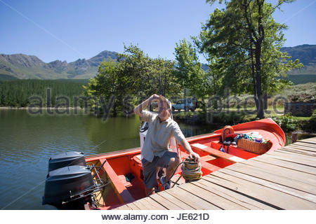 Senior man standing in moored motorboat beside lake jetty, tilting cap, admiring scenery, smiling - Stock Photo