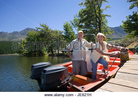 Senior couple standing in motorboat beside lake jetty, woman tying rope to mooring post, smiling, portrait - Stock Photo