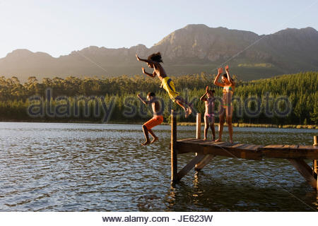 Family, in swimwear, standing on jetty, father and son (8-10) jumping into lake, side view - Stock Photo