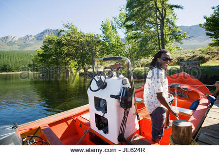 Man standing in motorboat beside lake jetty, leaning on rope tied to mooring post, side view, smiling, portrait - Stock Photo
