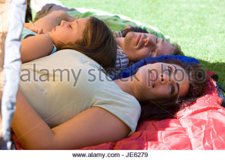 Family lying on sleeping bags in tent entrance on garden lawn, father and children (7-9) sleeping, mother daydreaming, - Stock Photo