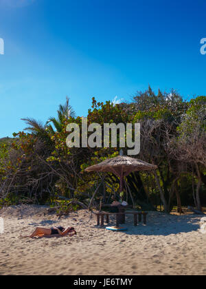 A woman sunbathing on Macaroni Beach Mustique, A white sand pristine beach with Azure Blue water. It's a beach for - Stock Photo