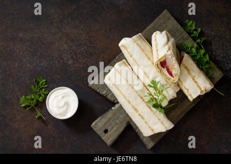 Shawarma pita bread with grilled chicken, fresh vegetables and cream sauce on a background of brown stone. Top view - Stock Photo