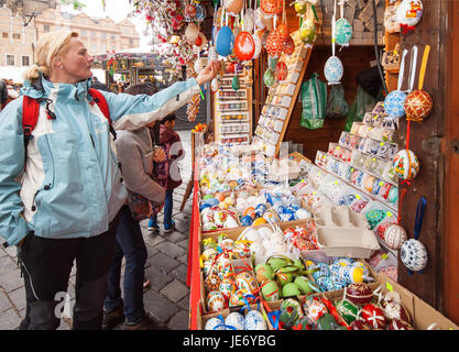 PRAGUE - APRIL 16th: Tourists viewing Easter Eggs on display in the market on Old Town Sq. on April 16th, 2017 in - Stock Photo