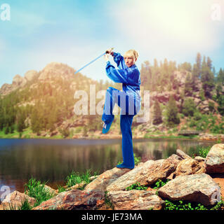 wushu master with sword meditation on the top of mountain