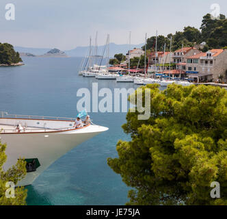 Two people relax on the prow of a large ocean going yacht in the harbour of Pomena on the island of Mljet in Croatia - Stock Photo