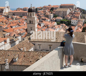 An Asian tourist taking a photograph of the medieval city of Dubrovnik on the Dalmation coast of Croatia - Stock Photo