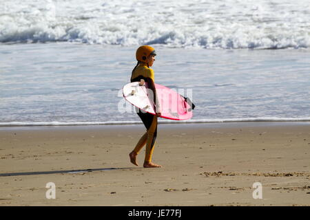 A young preteen surfer girl going surfing. - Stock Photo