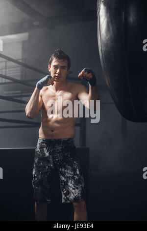 Active man with boxing wraps training punch for punching bag - Stock Photo