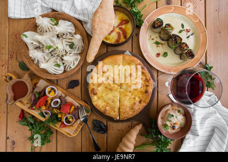 A lot of food on the wooden table. Georgian cuisine. Top view. Flat lay . Khinkali and Georgian dishes - Stock Photo