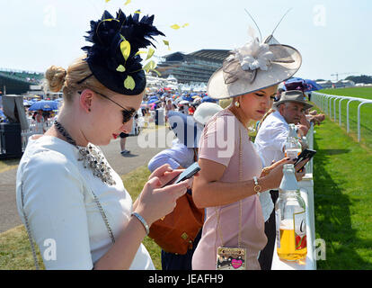 Beautiful young women watch race horses by the track at Ascot on a hot summers day. Their hats are exceptional and - Stock Photo