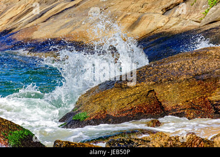 Wave crashing on the rocks of Red Beach beach at Urca, Rio de Janeiro - Stock Photo