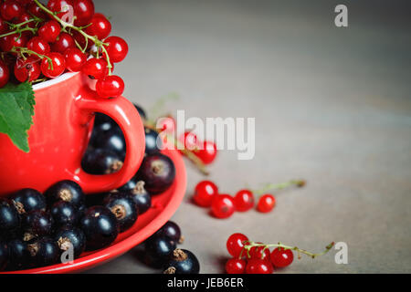 Ripe red and black currants on a wooden table. Summer still life. - Stock Photo