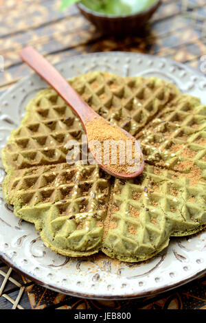 Homemade waffles with addition of matcha, pistachios, flax seeds. Decorated with coconut sugar. - Stock Photo
