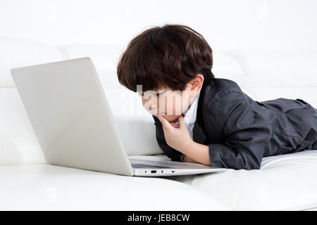 Asian Chinese little boy playing laptop on the couch in the living room at home - Stock Photo