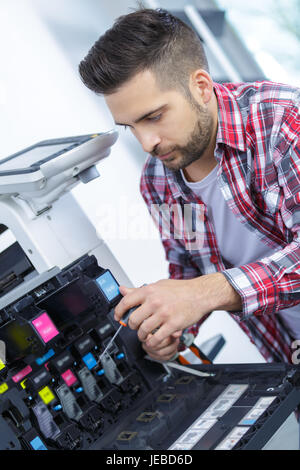 man fixing cartridge in photocopy machine at office - Stock Photo