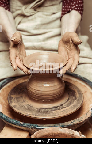 Close up of female hands working on potters wheel - Stock Photo