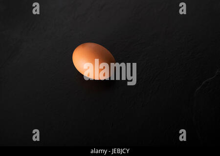 One raw egg over a black stone plate with copy space. - Stock Photo