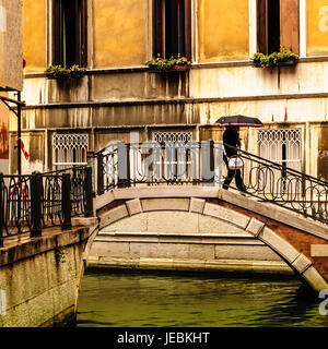 Women walking on bridge in the rain in Venice Italy.  One of the many small bridges in Venice. Our first day in - Stock Photo