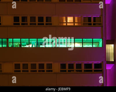 nighttime shot of council housing high flats with washing line still out late artificial light - Stock Photo