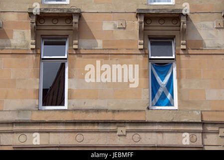 Scottish tenement windows with reflection of sandstone building and satire flag in the window - Stock Photo