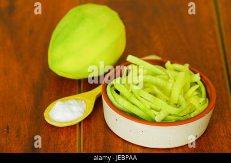 Close up shot of small sliced mango served with salt on a plate - Stock Photo