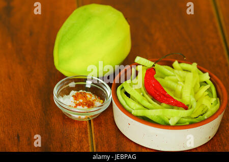 Close up shot of small sliced mango served with salt and a red chilli pepper on a plate - Stock Photo
