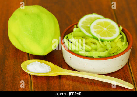 Close up shot of small sliced mango served with salt and lemon on a plate - Stock Photo