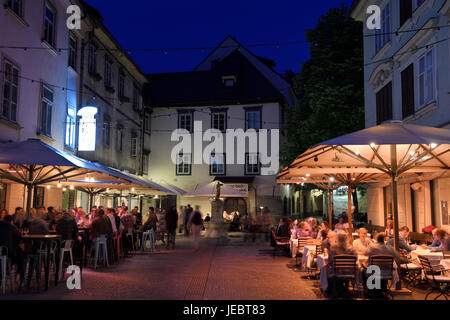 Nightlife outdoor restaurant cafes in Cobblestone Courtyard Ribji or Fish Square from Cankar Quay to Town Square - Stock Photo