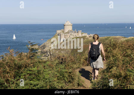 Europe, France, Brittany, Cote D' Emeraude, Cap Frehel, woman on footpath, in the background the castle fort la - Stock Photo