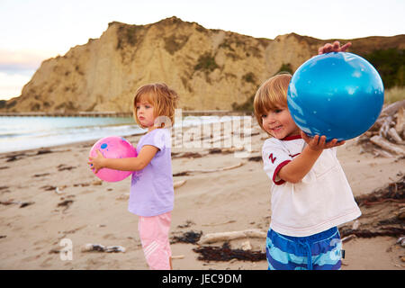 Children playing on the beach with balls Tolaga Bay (Māori: Uawa) - Stock Photo