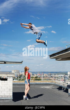 A loving couple of roofer on the roof. The girl watches as her boyfriend jumps from roof to roof. Romance and courage. - Stock Photo