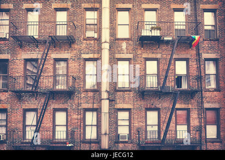 Old film retro style photo of a building with fire escape, one of New York City symbols, USA.